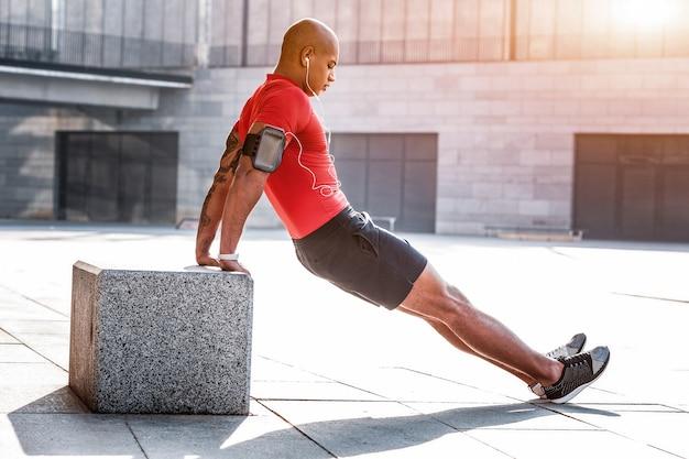 Sportliche aktivität. netter gutaussehender mann, der eine übung macht, während er sich auf sein training konzentriert