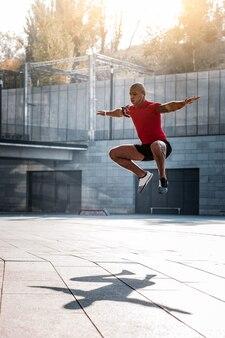 Sportliche aktivitäten. gut gebauter hübscher junger mann, der während der sportlichen aktivitäten aufspringt