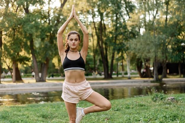 Sportliche aktivitäten im grünen park junge frau praktiziert yoga im morgenpark in der nähe des sees