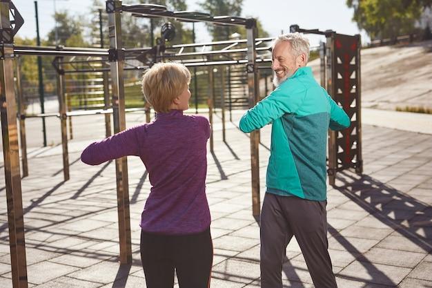Sportliche aktivitäten in den frühen morgenstunden aktives reifes familienpaar in sportbekleidung, das sich ausübt