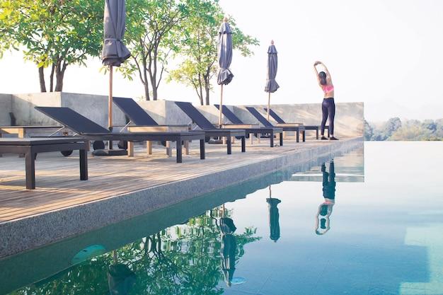 Sportliche asiatische frau, die nahe swimmingpool trainiert. gesundes lebensstilkonzept