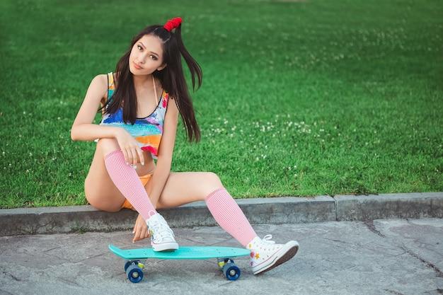 Sportliche asiatische frau mit skateboard