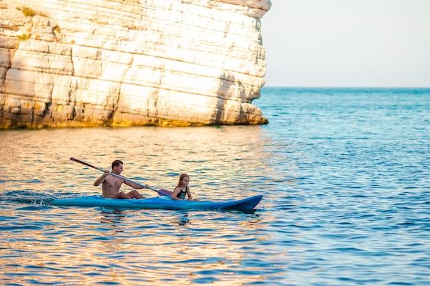 Sportliche attraktive familie, die zusammen auf meer kayak fährt