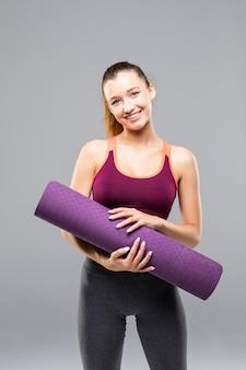 Sportliche attraktive frau, die yogamatte vor oder nach fitnessklasse isoliert hält