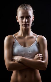 Sportliche bauchfrau, die lokal über dunklem hintergrund steht