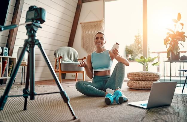 Sportliche bloggerin in sportbekleidung, die mit hanteln und einem laptop auf dem boden sitzt und der kamera zu hause im wohnzimmer ein glas sporternährung zeigt. sport- und erholungskonzept.