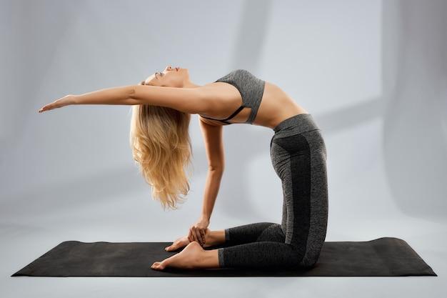 Sportliche blonde frau macht yogaübungen