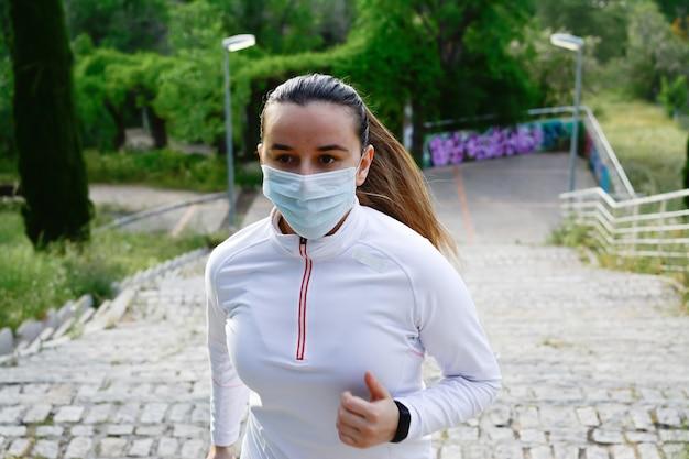 Sportliche blonde frau mit einer maske auf ihrem gesicht und einem pferdeschwanz, der in einem park läuft. laufendes konzept.