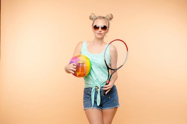 Sportliche blondine, die frischen saft trinkt und sport treibt