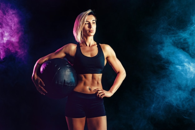 Sportliche blondine in der modernen sportkleidung, die mit medizinball aufwirft. foto der muskulösen frau auf dunkler wand mit rauche. kraft und motivation.