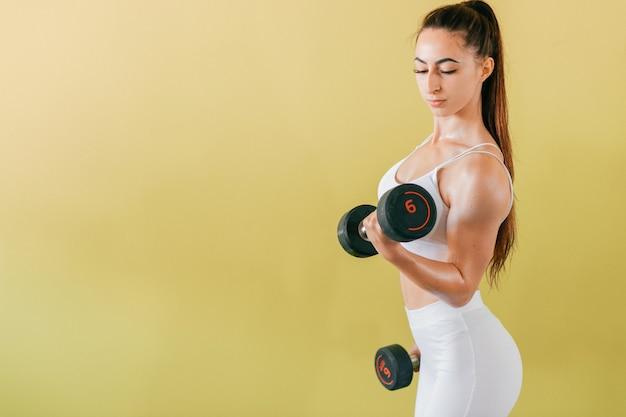 Sportliche bodybuilderin mit hanteln. schönes brünettes mädchen mit den muskeln, die gewichte heben