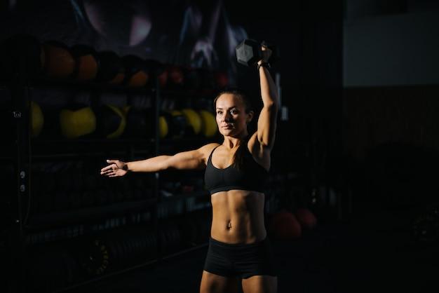Sportliche bodybuilderin mit perfektem muskulösem körper in schwarzer sportbekleidung hebt kettlebell während des krafttrainings über den kopf. konzept des gesunden lebensstils und des trainings in einem modernen dunklen fitnessstudio.