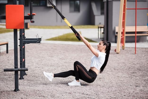 Sportliche brünette frau in einem weißen t-shirt trainiert tagsüber mit hilfe von fitnessgurten auf dem spielplatz