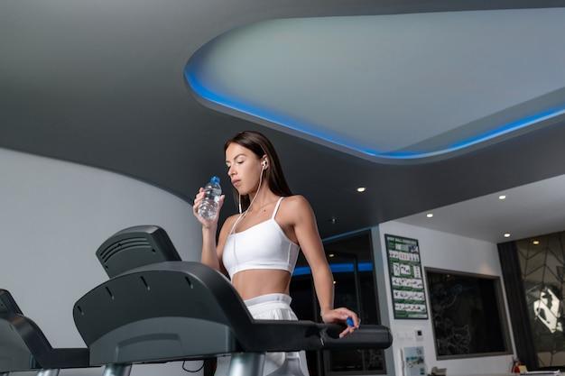 Sportliche brünette in einem weißen sportoberteil mit kopfhörern und einem telefon in ihren händen, die beim stehen auf einem laufband im fitnessstudio posieren. trinkwasser aus einer flasche.
