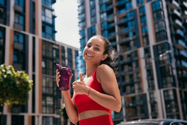 Sportliche entzückende lächelnde junge frau mit dunklem haar, das roten bh trägt, der sportflasche hält und daumen hoch