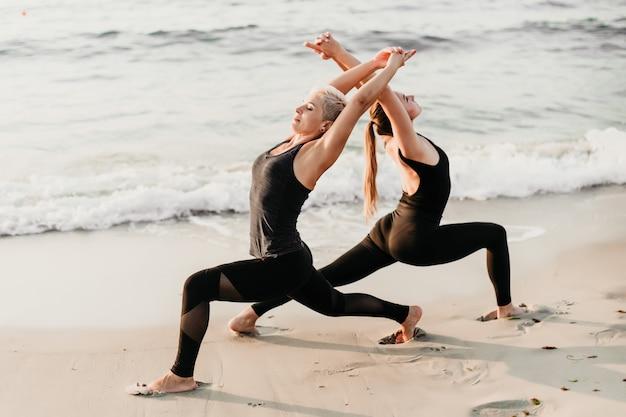 Sportliche erwachsene frau mit jungem eignungsmädchen-übungsyoga auf dem strand nahe ozean zusammen