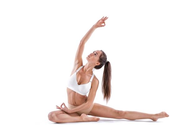 Sportliche fit schöne frau in sportbekleidung, die isolierten weißen hintergrund herausarbeitet. control balance übung, studio in voller länge.