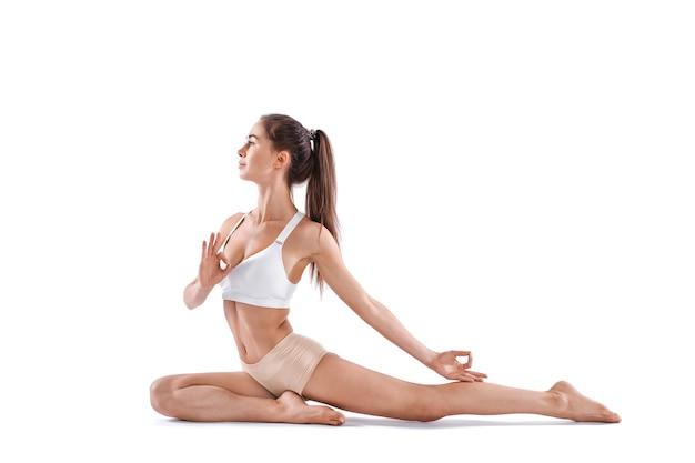 Sportliche fit schöne frau in sportbekleidung, die yoga lokalisierten weißen hintergrund tut. gleichgewicht zwischen körperlicher und geistiger entwicklung.