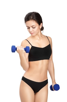 Sportliche fitnessfrau, die blaue hanteln auf weiß anhebt
