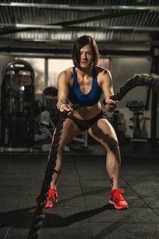 Sportliche fitnessfrau, die funktionelle trainingsübung mit kampfseilen an der turnhalle tut