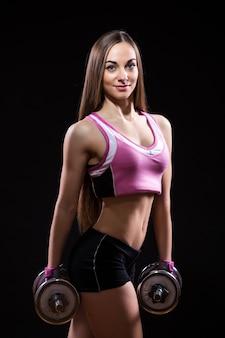 Sportliche fitnessfrau mit hanteln lokalisiert auf schwarzem hintergrund