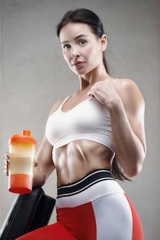 Sportliche fitnessfrau trinkt wasser aus orangenschüttler beim training im fitnessstudio. recht kaukasisches athletisches mädchen. fitness- und sportkonzept.