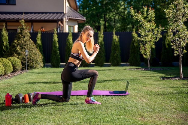 Sportliche fitnesstrainerin strecken sich vor dem online-training im garten