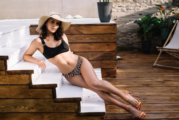 Sportliche frau am schwimmbad im tropischen resort, das ihre ferien genießt