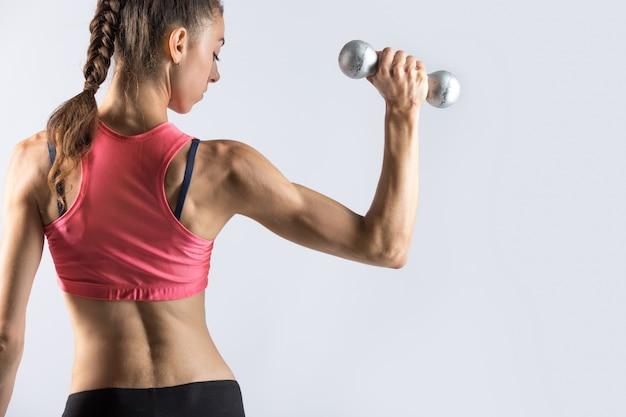 Sportliche frau arbeitet mit gewichten aus. rückansicht