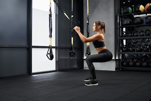 Sportliche frau beim kniebeugen mit fitnessgurten