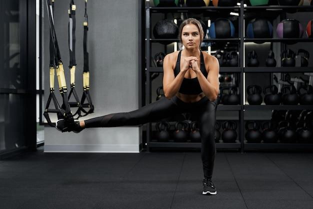 Sportliche frau beim kniebeugen mit trx-system