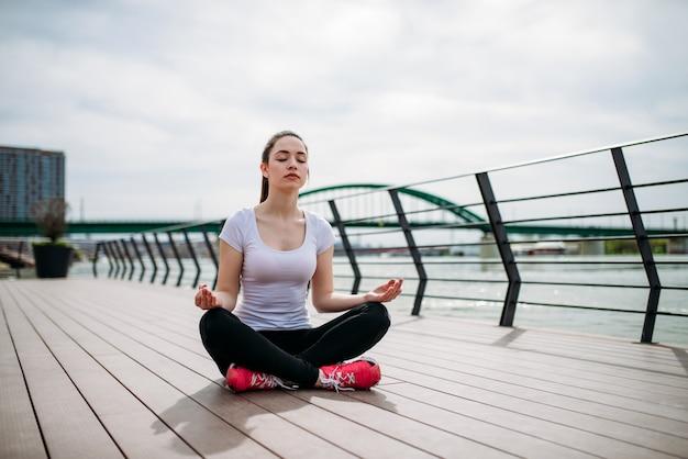 Sportliche frau der jungen hübschen eignung, die das joga im freien an der flussküste tut.