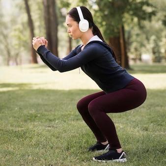 Sportliche frau der seitenansicht, die draußen trainiert