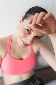 Sportliche frau des porträts, die nach dem training zu hause ruht