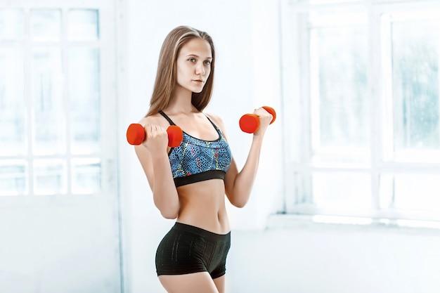 Sportliche frau, die aerobic-übung mit roten dummköpfen tut