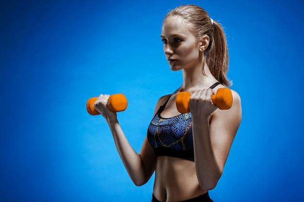 Sportliche frau, die aerobic-übung mit roten hanteln macht