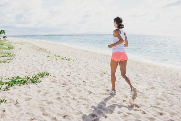 Sportliche frau, die am strand joggt