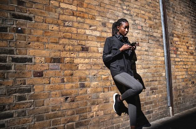 Sportliche frau, die an einer backsteinmauer sich lehnt