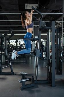 Sportliche frau, die an klimmzugmaschinen im fitnessstudio trainiert exercising