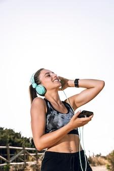 Sportliche frau, die an musik mit ihren kopfhörern genießt