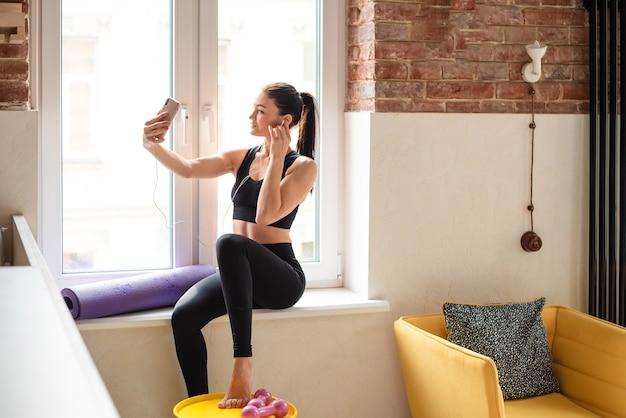 Sportliche frau, die auf der fensterbank sitzt und modernes smartphone und kopfhörer zum musikhören verwendet. junge dame in activewear, die sich nach dem häuslichen training ausruht.