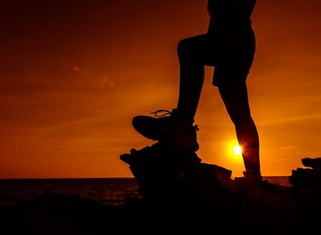 Sportliche frau, die auf die klippe klettert. erfolgs- und zielkonzept. stark und gesund für outdoor-aktivitäten. frischer start in den tag