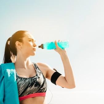 Sportliche frau, die auf himmelhintergrund trinkt