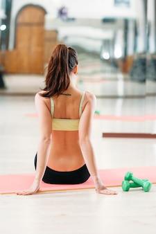 Sportliche frau, die auf matte vor dem training im fitnessstudio sitzt