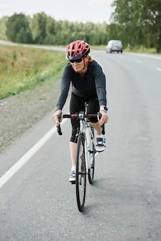 Sportliche frau, die auf rennrad fährt, während sie auf der landstraße trainiert