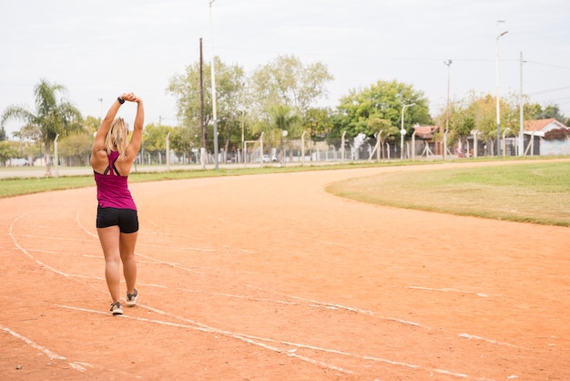 Sportliche frau, die auf stadionsbahn ausdehnt