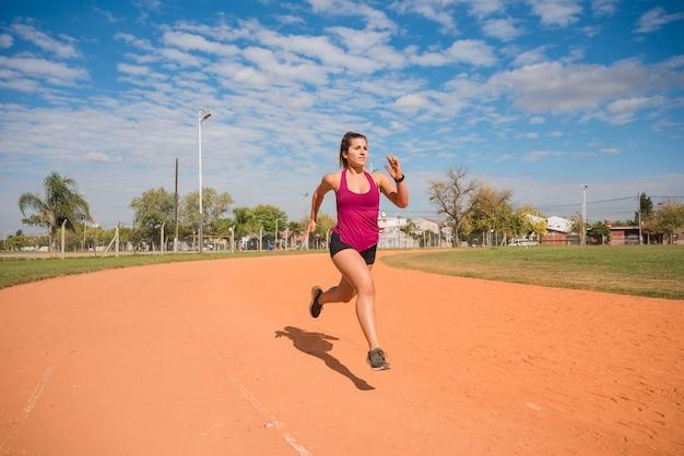 Sportliche frau, die auf stadionsbahn läuft
