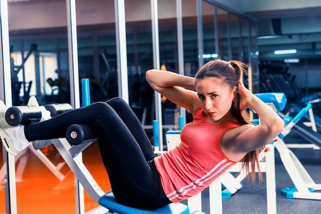 Sportliche frau, die bauchmuskeltraining unter verwendung der trainingsvorrichtung in einer turnhalle tut
