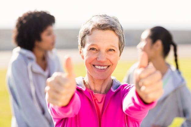 Sportliche frau, die daumen vor freunden tut