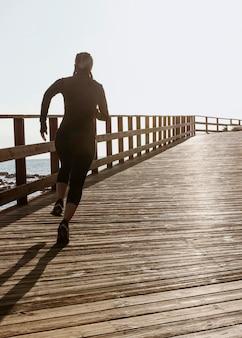 Sportliche frau, die durch den strand mit kopienraum joggt